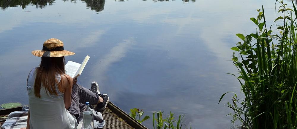 Woman reading by a lake.